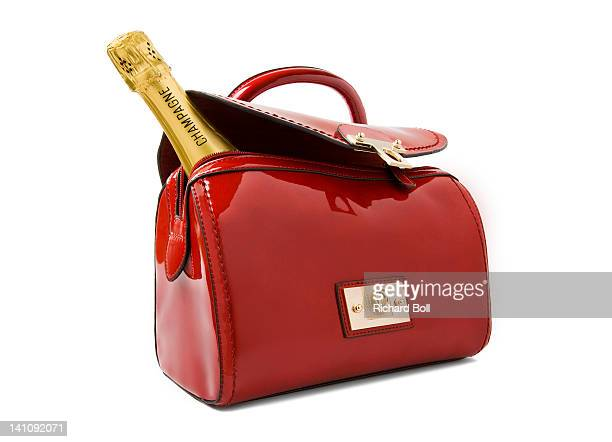 A bottle of Champagne in a red handbag.