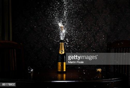 bottle of champange on table exploding cork : Stock Photo