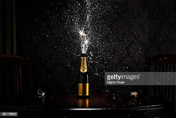 bottle of champange on table exploding cork
