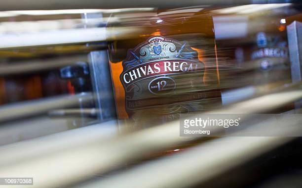 A bottle of Chivas Regal whisky travels along a conveyor belt at the Pernod Ricard SA bottling plant in Paisley UK on Thursday Nov 18 2010 Pernod...