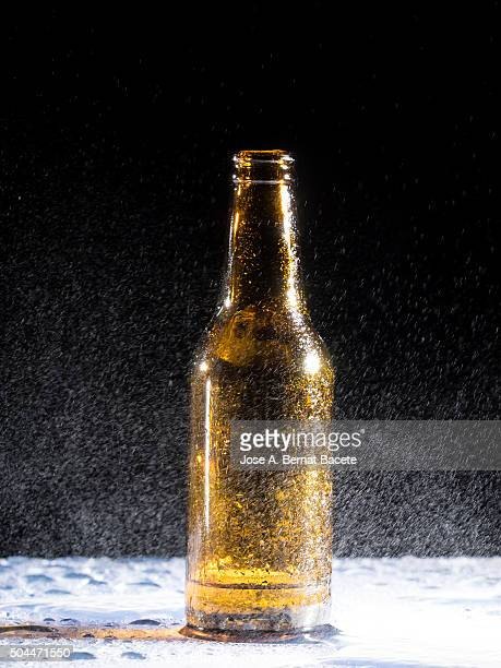 Bottle of cold beer on an empty table with water drops