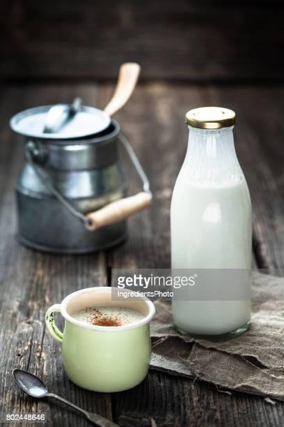 Bouteille de yaourt frais et une tasse sur la table en bois.