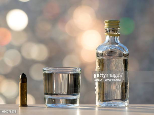 Bottle of gin close to a bullet, concept of which the alcoholism kills