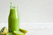 bottle of green smoothie with fresh kiwi and banana fruits and berries over white wooden background. healthy breakfast