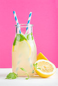 Bottle of homemade lemonade with ice and lemons, paper straws and bright purple background, selective focus