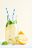 Bottle of homemade lemonade with ice and lemons, paper straws and pastel yellow background, selective focus