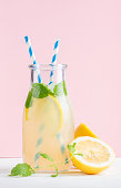 Bottle of homemade lemonade with ice and lemons, paper straws and pastel pink background, selective focus