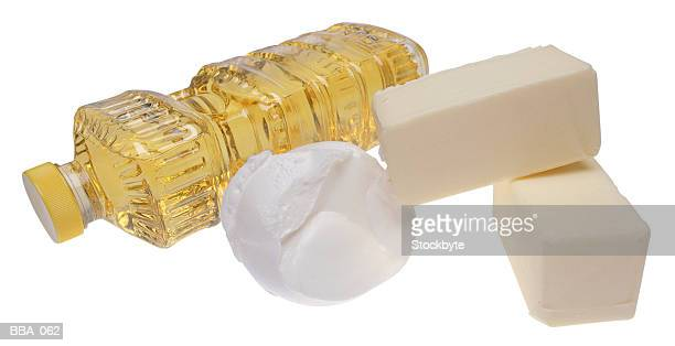 Bottle of oil on its side, two bricks of butter, scoop of shortening