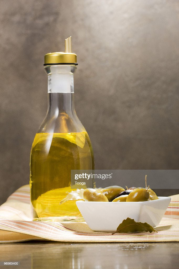 Bottle of olive oil with bowl of olives : Stock Photo