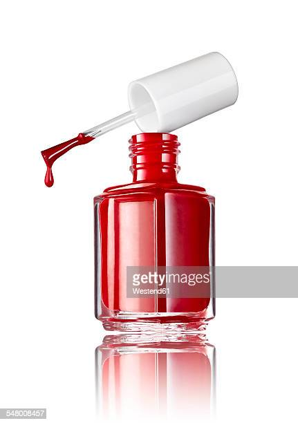 Bottle of red nail polish in front of white background