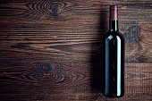 Bottle of red wine on dark wooden background from top view
