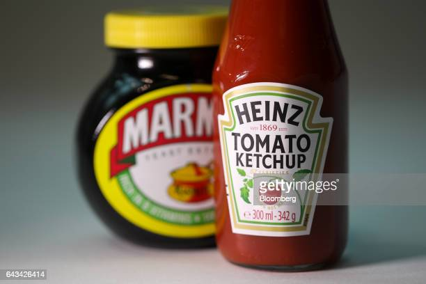 A bottle of tomato ketchup manufactured by Kraft Heinz Co right stands next to a jar of Marmite manufactured by Unilever NV in this arranged...