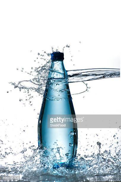 A bottle of water being hit by a jet of water
