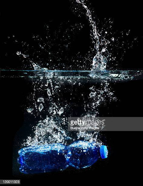 Bottle of water splashing in water