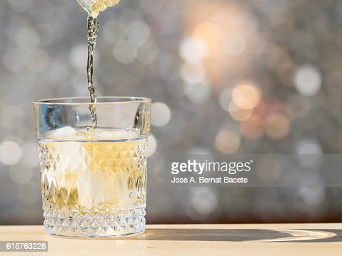 Bottle of whiskeys filling a glass with ice on the table of a bar outdoors : Stock Photo