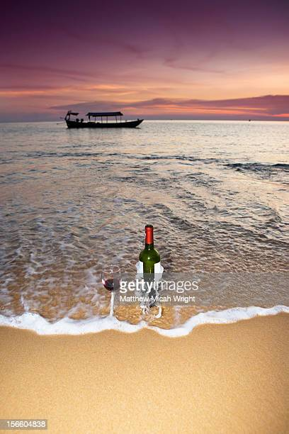 A bottle of wine and a glass sit on the sand