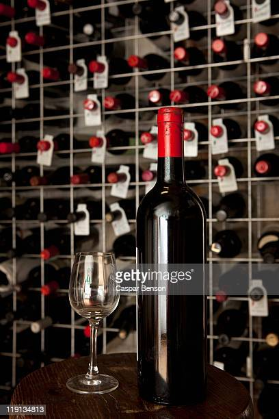 A bottle of wine and a wineglass in a cellar