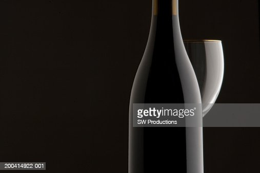 Bottle of wine next to wine glass, close-up