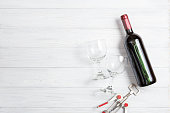 bottle of wine with wine glass on white wooden background.
