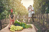 A bottle of wine, vine and glass of wine on the background of the vineyard and a couple of people in love
