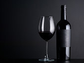 bottle red of wine with a glass on a black background