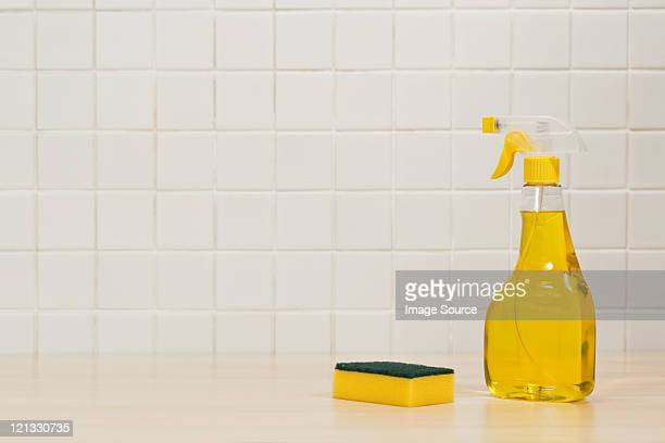 Bottle of yellow cleaning fluid and cleaning sponge
