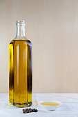 bottle olive oil with  test plate and Peppercorns on brown and white background