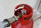 Filling red lpg gas bottle, overhead shot with selective focus