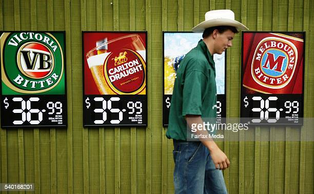 A bottle shop employee walks past beer advertisements on a shop wall in Tamworth New South Wales 18 January 2005 AFR Picture by LOUIE DOUVIS