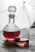Bottle whiskey and Glass of whiskey with ice and light blurred background.