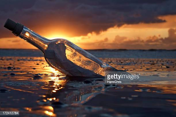 A bottle with a message washed up in a beach during sunset