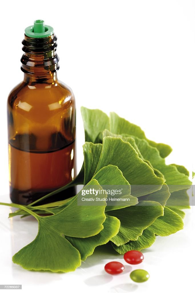 Bottle with ginkgo leaves and pills. close-up