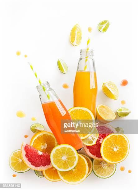 Bottled citrus juice with fresh citrus slices on white background. Juice flowing or splashing out from the bottle. Refreshing citrus juice design element.