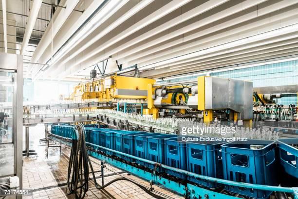 Bottles and crates on conveyor belt in bottling facility, bottling mineral spring water