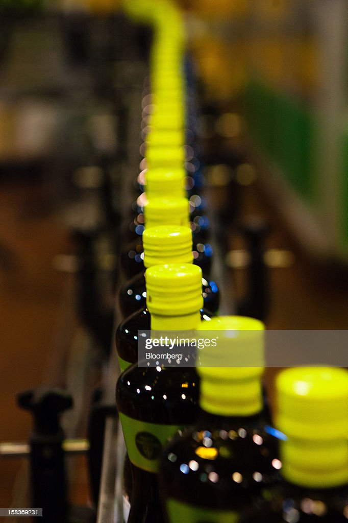 Bottles move along the production line after being filled with olive oil at the Gallo Worldwide plant in Abrantes, Portugal, on Friday, Dec. 14, 2012. The Iberian nation has already been granted more time to narrow its budget shortfall after tax increases failed to bring in enough money to meet forecasts as the economy heads for a third year of contraction in 2013. Photographer: Mario Proenca/Bloomberg via Getty Images