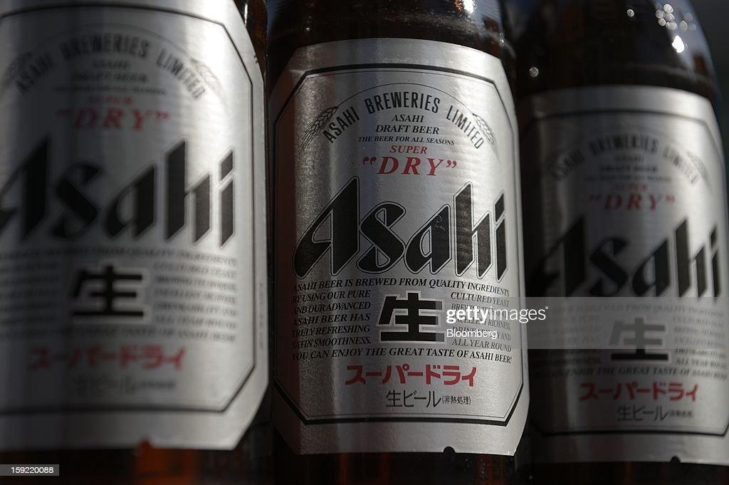 Bottles of Asahi Breweries Ltd. Asahi Super Dry beer are arranged for a photograph in Kawasaki, Kanagawa Prefecture, Japan, on Wednesday, Jan. 9, 2013. Suntory, Kirin Holdings Co. and Asahi Group Holdings Ltd., have sought growth overseas as a declining population damps domestic demand. Photographer: Akio Kon/ Bloomberg