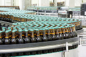 Bottles of beer on conveyor in brewery