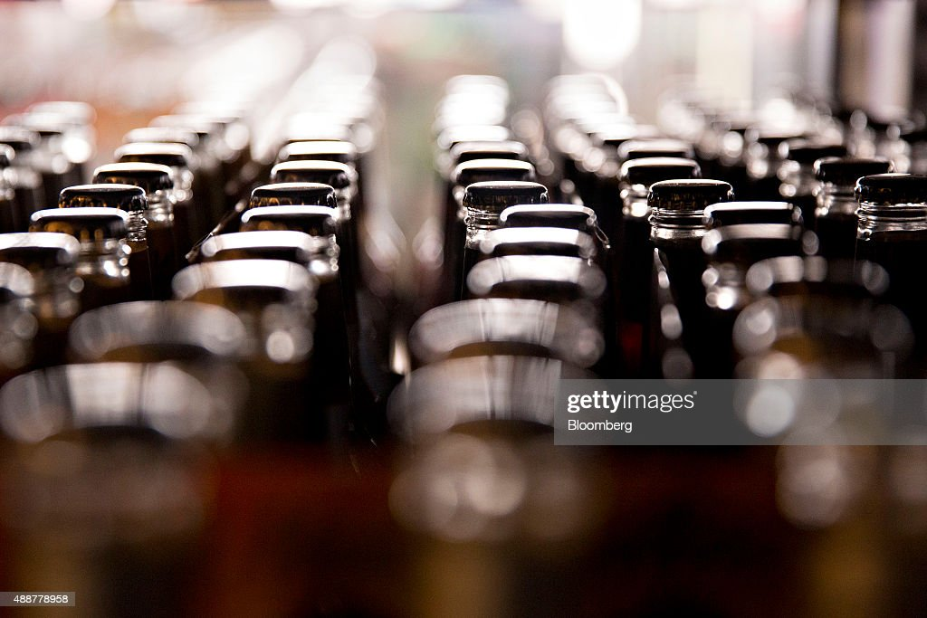 Bottles of beer sit in a liquor store cooler in Chillicothe Illinois US on Thursday Sept 17 2015 AnheuserBusch InBev NV unveiled plans to acquire...