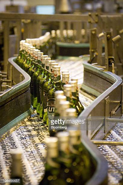 Bottles of Castle Lite beer sit on the production line after labeling at the company's Alrode depot in Johannesburg South Africa on Thursday Oct 14...