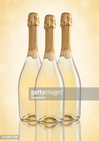 Bottles of champagne golden yellow color on golden : Stock Photo