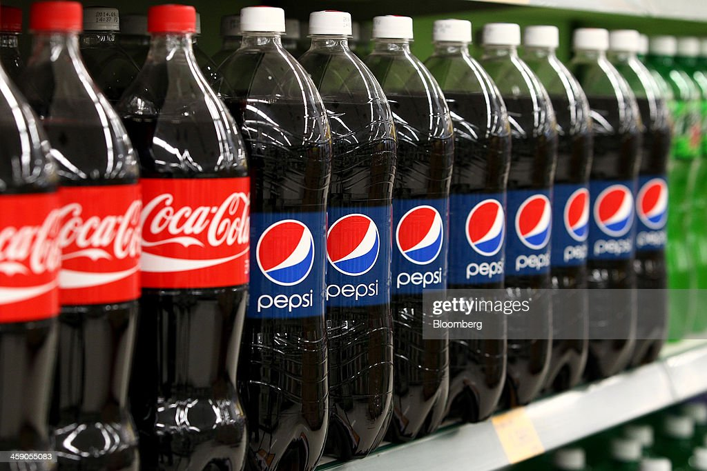 Bottles of Coca-Cola Co. soda and PepsiCo Inc. Pepsi soda are displayed for sale at an E-Mart Co. store, a subsidiary of Shinsegae Co., in Incheon, South Korea, on Saturday, Dec. 21, 2013. Consumer prices climbed 0.9 percent in November from a year earlier after a 0.7 percent increase in October that was the smallest gain since July 1999. Photographer: SeongJoon Cho/Bloomberg via Getty Images