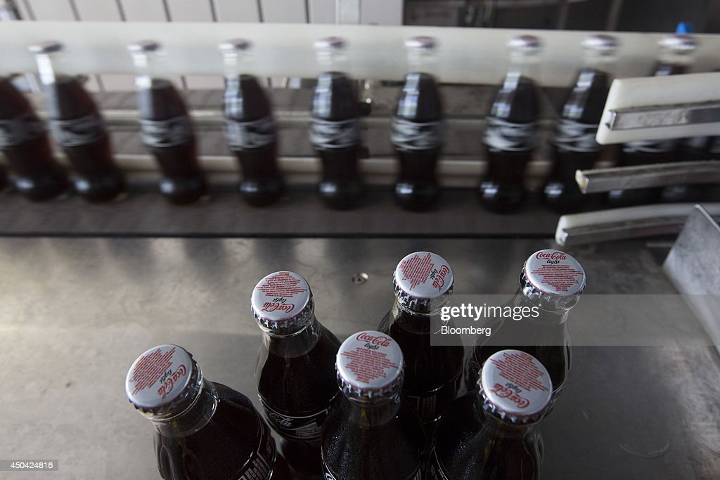 Bottles of Coca-Cola Light, also known as diet Coke, travel along the production line during manufacture at the Lanitis Bros Ltd. bottling plant, part of the Coca-Cola Hellenic Group, in Nicosia, Cyprus, on Tuesday, June 10, 2014. Zug, Switzerland-based Coca-Cola Hellenic Bottling Co., which distributes Coca-Cola products in countries including Russia, wants to move away from using imported sugar for its Russian operations by 2015. Photographer: Andrew Caballero-Reynolds/Bloomberg via Getty Images