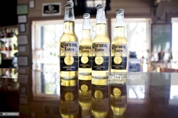 Bottles of Constellation Brands Inc Corona beer stand on a counter in an arranged photograph at a restaurant in Ottawa Illinois US on Tuesday June 27...
