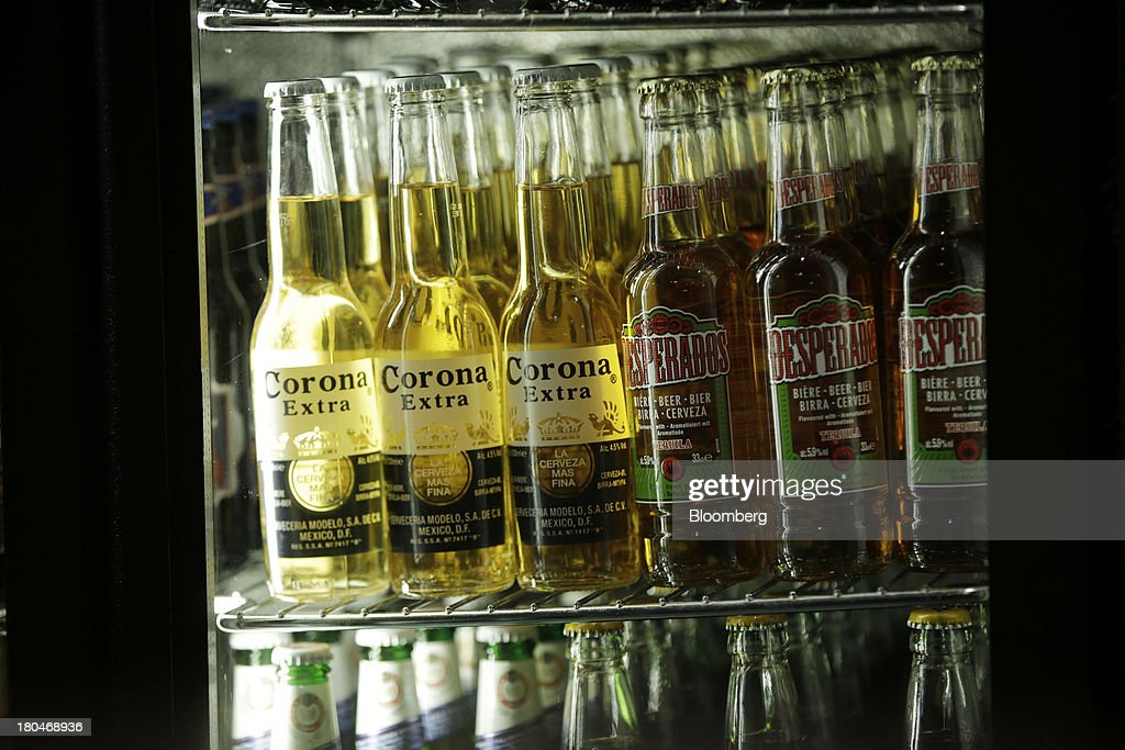 Bottles of Corona Extra, left, produced by Grupo Modelo SAB, and Desparados lager beer, produced by Heineken NV, sit on display inside a refrigerator at a JD Wetherspoon Plc pub in London, U.K., on Friday, Sept. 13, 2013. JD Wetherspoon, who reported full year sales today, are planning to move into the Irish market next year, Chairman Tim Martin said in a recent interview. Photographer: Matthew Lloyd/Bloomberg via Getty Images
