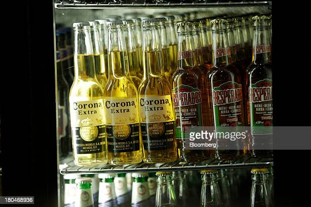Bottles of Corona Extra left produced by Grupo Modelo SAB and Desparados lager beer produced by Heineken NV sit on display inside a refrigerator at a...