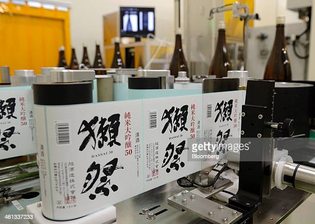 Bottles of Dassaibranded sake pass through a labeling machine at the Asahishuzo Co brewery manufacturing Dassaibranded sake in Iwakuni Yamaguchi...