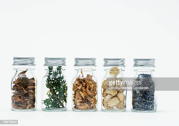 Bottles of dried flowers, herbs and wood shavings
