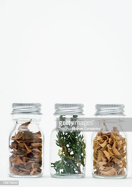 Bottles of dried flowers, herbs and wood shavings