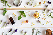 Bottles of essential oil with frankincense, lavender, thyme, rosemary, myrrh, oregano, helichrysum on a white background