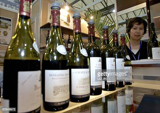 Bottles of French red wine are displayed as an exhibitor stands by at an international food exhibition in Shanghai 19 May 2005 AFP PHOTO/LIU Jin